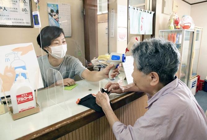 An employee checks the temperature of a customer at the reception counter of Tsuki no Yu in Tokyo. MUST CREDIT: Japan News-Yomiuri photo