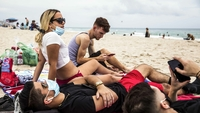 In the city of Miami Beach, Daniel Milian, from right, Miguel Martinez and Laura De Armas relax by the sea in South Beach on Friday with varying mask use. Whether to wear a mask in public has become fiercely controversial. MUST CREDIT: Photo by Scott McIntyre for The Washington Post