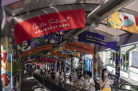 Pedestrians ride on an escalator past banners promoting local tourism in Hong Kong on Friday, June 19, 2020. MUST CREDIT: Bloomberg photo by Chan Long Hei