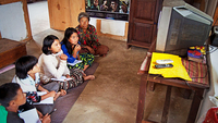 Dechen Wangmo (blue shirt) with her classmates attend an e-learning session on national television at a neighbour's house in Tsangkhar village under Phongmey in Trashigang (Photo: UNICEF Bhutan)