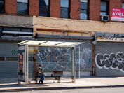A person sits at a bus stop next to closed businesses in the New York borough of Brooklyn on June 17, 2020. MUST CREDIT: Bloomberg photo by David Dee Delgado.