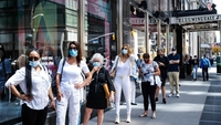 Shoppers wearing protective masks wait in line to enter Bloomingdale's in New York on June 22, 2020. MUST CREDIT: Bloomberg photo by Jeenah Moon