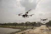 Drones spray pesticide over a newly planted rice field during a demonstration flight on Chongming Island in Shanghai on May 18, 2020. The U.S. is culling Chinese-made drones from government fleets. MUST CREDIT: Bloomberg photo by Qilai Shen