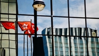 The Chinese national flag and the Hong Kong Special Administrative Region flag are seen in a reflection on a building in Tsim Sha Tsui, Hong Kong, June 30, 2020. (RAYMOND CHAN / CHINA DAILY)