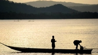 A fisherman starts his boat engine as his son looks on along the Mekong River in Luang Prabang, Laos. MRC