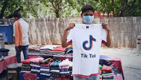 A vendor poses in front of his stall with a T-shirt bearing the logo of the video-sharing application TikTok in New Delhi on Tuesday, June 30, 2020. The Indian government announced a decision on Monday to block 59 Chinese apps citing