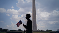 Hassan Elhadi, 16, sells American flags near the Washington Monument on Saturday in Washington, D.C.  Photo by Evelyn Hockstein for The Washington Post