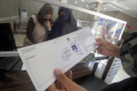 A job seeker obtains an AK/1 card, also known as a yellow card, designated for unemployed citizens, at the Bogor regency Manpower Agency in Cibinong, Bogor, West Java, on June 12. (Antara/Yulius Satria Wijaya)
