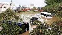 Vehicles are seen washed up in a pond near a shrine in Hitoyoshi, Kumamoto Prefecture, on July 6, 2020. MUST CREDIT: Japan News-Yomiuri