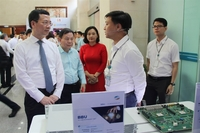 Minister of Information and Communications Nguyễn Mạnh Hùng (left) looks at digital technologies on display. — File Photo
