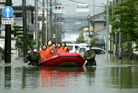 Children are evacuated by a boat with the help of Self-Defense Forces personnel Tuesday morning after staying overnight at an elementary school in an inundated area in Omuta, Fukuoka Prefecture. (The Yomiuri Shimbun)