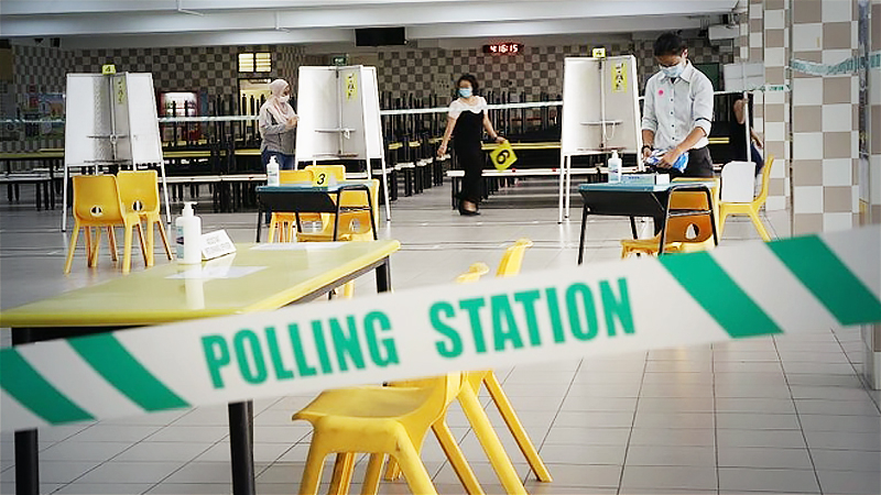 At Chung Cheng High School in Goodman Road yesterday, public servants set up the polling station, putting in place safe-distanced polling booths, temperaturetaking points, sanitising products and floor markings for spaced queues to ensure the safety of voters. PHOTO: LIANHE ZAOBAO