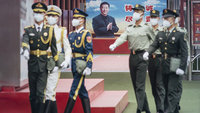 Members of the People's Liberation Army honor guards walk past a banner depicting Chinese president Xi Jinping near the Forbidden City in Beijing on May 21, 2020. MUST CREDIT: Bloomberg photo by Qilai Shen.