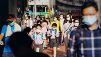 Pedestrians and schoolchildren wearing masks walk along a sidewalk in Hong Kong on July 10, 2020. A surge in coronavirus cases after a long stretch without infections is forcing the financial hub to reinstate restrictions that had been loosened. MUST CREDIT: Bloomberg photo by Roy Liu