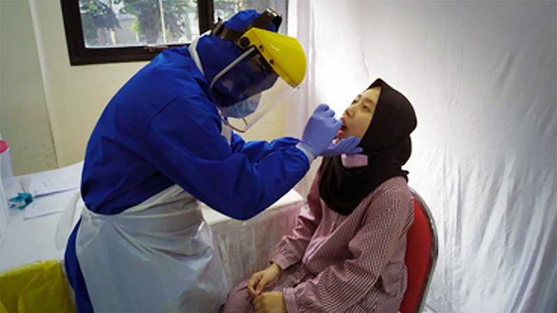 A nurse conducts a swab test, also known as a polymerase chain reaction (PCR) test, on a woman at Tanah Abang district office in Jakarta on June 21. The swab test session was hosted by the Indonesian Heart Foundation in cooperation with Bunda Hospital, Good Doctor and Grab Health. (JP/P.J. Leo)