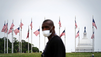 A pedestrian wears a mask while walking across the street from the World War II Memorial in Washington, D.C. CREDIT: Washington Post photo by Matt McClain