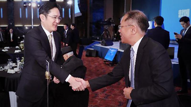 Samsung heir Lee Jae-yong shakes hands with Hyundai Motor Group heir Chung Euisun in January. (Yonhap)