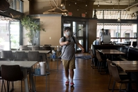 A worker sprays sanitizing disinfectant in the dining area of a restaurant in Mansfield, Ohio on July 13., 2020. MUST CREDIT: Bloomberg photo by Ty Wright.