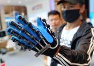 A visitor experiences a hand rehabilitation equipment at an international rehabilitation aids industry and service expo in Qinhuangdao, Hebei province. [Photo by Cao Jianxiong/For China Daily]