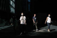 Pedestrians walk in an alleyway between commercial buildings in Hong Kong on July 22, 2020. (ANTHONY WALLACE / AFP)