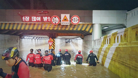 Firefighters launch rescue efforts Thursday at an underpass in Busan where three people died after being trapped inside due to heavy rainfall. (Busan Metropolitan Police Agency)