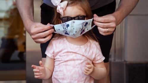 Matt Serenius helps his daughter Sloane Serenius, 2, put on her mask in Washington last week. MUST CREDIT: Photo by Amanda Andrade-Rhoades for The Washington Post.