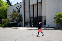 A shopper wears mask while passing in front of a Lord & Taylor Store in Novi, Mich., on June5. (Emily Elconin/Blomberg News)