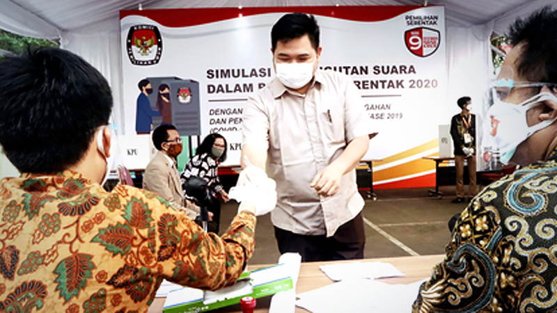 A member of a polling station working committee (KPPS) hands over plastic gloves to a voter during a simulation for the 2020 simultaneous regional elections in the grounds of the General Elections Commission (KPU) in Jakarta on July 22. (JP/Dhoni Setiawan)