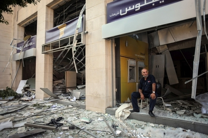 A private security guard sits at the entrance of a destroyed bank branch in Beirut, Lebanon, on Aug. 5. MUST CREDIT: Bloomberg photo by Hasan Shaaban.