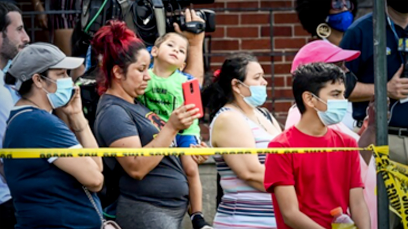 Neighbors watch first responders after an explosion destroyed three homes and killed a person in Baltimore on Monday, Aug. 10, 2020. MUST CREDIT: Washington Post photo by Bill O'Leary