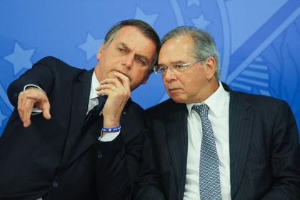 Jair Bolsonaro, Brazil's president, left, speaks with Paulo Guedes, Brazil's economy minister, in Brasilia on July 16, 2019. CREDIT: Bloomberg photo by Andre Coelho.