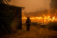 Flames from a backfire move away from a barn threatened by the Walbridge Fire Thursday. CREDIT: Photo for The Washington Post by Stuart W. Palley