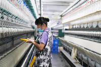 A woman works at the workshop of a textile company in Qinggang county, Northeast China's Heilongjiang province, April 16, 2020. [Photo/Xinhua]