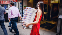 A pedestrian wearing a protective mask carries FedEx boxes in the Diamond District of New York on June 10, 2020. MUST CREDIT: Bloomberg photo by Nina Westervelt.
