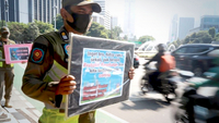 Jakarta Public Order Agency (Satpol PP) officers carry posters calling on residents to comply with government-imposed health protocols during rush hour in Senayan, South Jakarta, on Monday. (JP/Dhoni Setiawan)