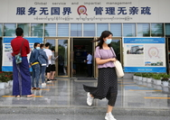 People wearing masks wait outside Ruili city's service center for foreign personnel in Yunnan province on Aug 20. ZHANG WEI/CHINA DAILY