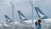 Aircraft operated by Cathay Pacific Airways are seen through a barbed-wire fence as they stand parked on the tarmac at Hong Kong International Airport in Hong Kong, on June 9, 2020. (ROY LIU/CHINA DAILY)