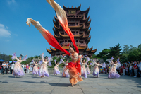 Visitors watch a dance performed in front of Yellow Crane Tower in Wuhan, Hubei province, on Thursday. The scenic area arranged traditional performances to welcome tourists from across the country eager to travel now that COVID-19 is controlled. HU JIUSI/FOR CHINA DAILY