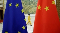 In this file photo, an attendant walks past EU and China flags ahead of the EU-China High-level Economic Dialogue at Diaoyutai State Guesthouse in Beijing, China, June 25, 2018. (Photo / Agencies)