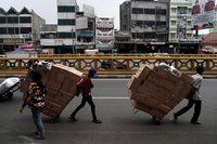 Workers transport carts loaded with boxes at Tanah Abang market in Jakarta, Indonesia, on Aug 4, 2020. (PHOTO / BLOOMBERG)