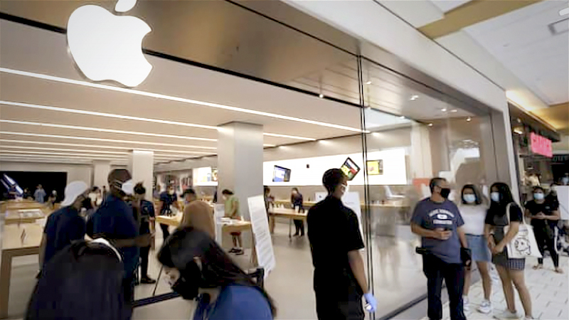 Shoppers stand in line at the Apple store at the Queens Center shopping mall in the Queens borough of New York, on Sept. 9, 2020. MUST CREDIT: Bloomberg photo by Peter Foley.