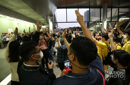 Supporters of the pro-democracy movement sing the national anthem while giving three-finger salutes against dictatorship. Photo by Wanchai Kraisornkhajit