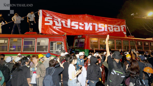Protesters gather on October 21 in Bangkok. A red banner reads: Coup will be met with our defiance.