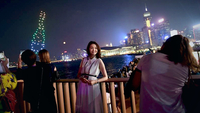 A woman poses for photos in from of Victoria Harbour while attending the opening ceremony of Hong Kong Wine and Dine Festival at Central Harbourfront, Hong Kong, Jan 4, 2019.
