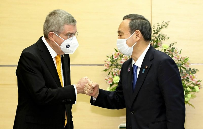 International Olympic Committee President Thomas Bach, left, and Prime Minister Yoshihide Suga put their fists together at the Prime Minister's Office on Monday. (The Yomiuri Shimbun)