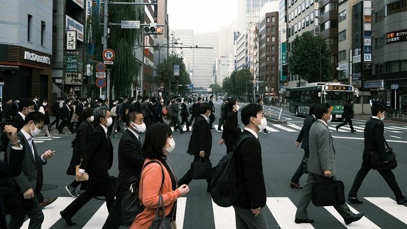 Pedestrians wearing protective masks cross a road in Tokyo on Nov. 19, 2020. MUST CREDIT: Bloomberg photo by Soichiro Koriyama.