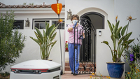 A healthcare worker receives groceries delivered with a Starship Technologies robot in Mountain View, California, on May 18. MUST CREDIT: Bloomberg photo by Nina Riggio.