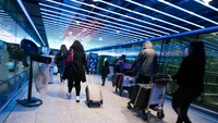 Passengers walk toward the check-in area at London Heathrow Airport in London on Dec. 19, 2020. MUST CREDIT: Bloomberg photo by Chris Ratcliffe
