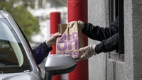 An employee wearing protective gloves hands an order to a customer through a drive-through window at a McDonald's in Oakland, Calif., on April 9, 2020. MUST CREDIT: Bloomberg photo by David Paul Morris