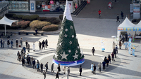 People wait in a long line around a large Christmas tree to get tested for COVID-19 at a screening center in Seongnam, just south of Seoul, on Christmas Eve on Thursday. (Yonhap)